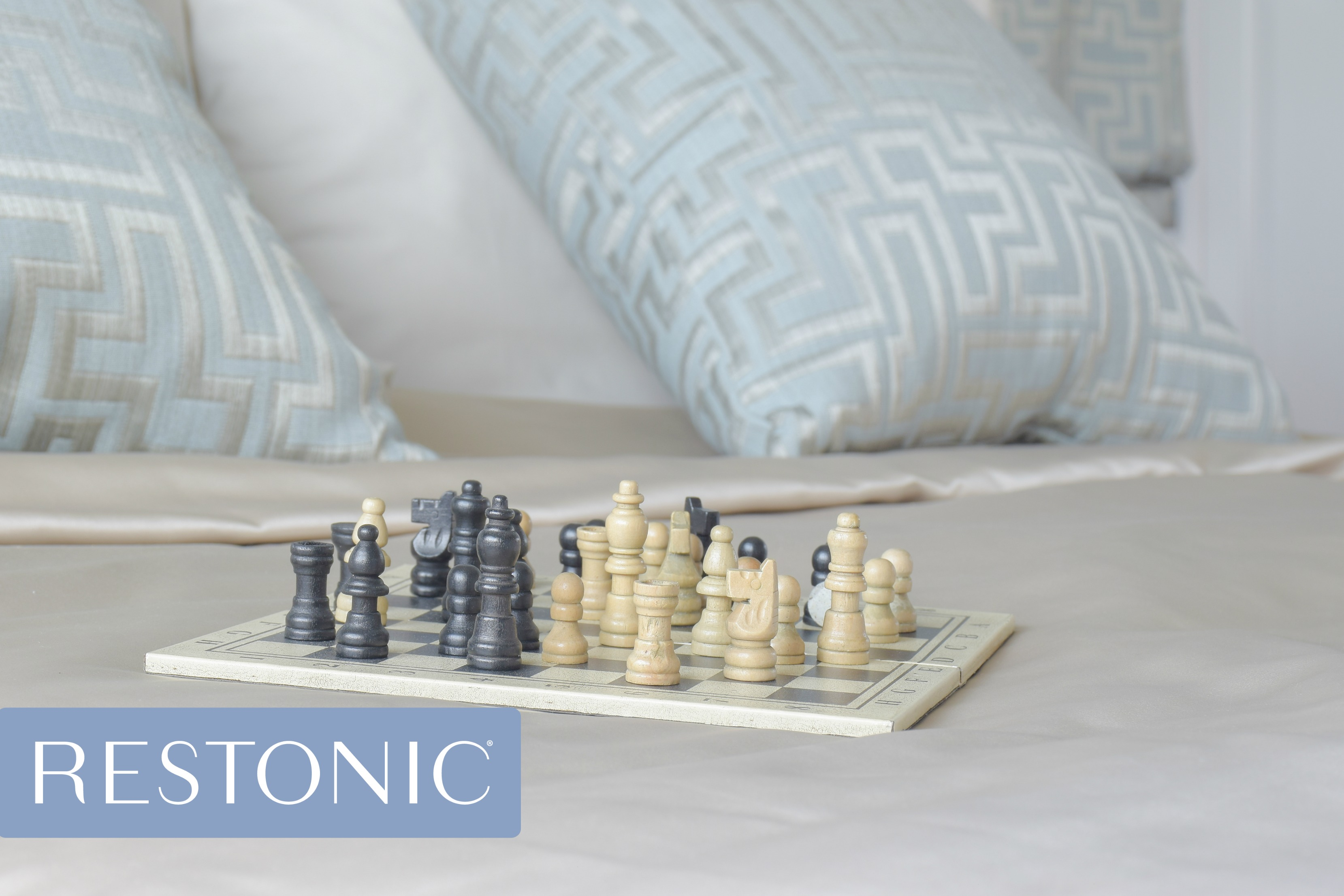 A new Restonic mattress with a chess board sitting on top.