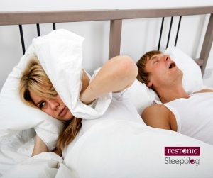Woman covering her ears because her partner is snoring | Benefits of sleeping alone.