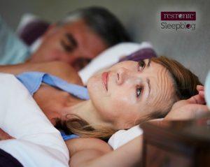 Woman laying awake at night due to anxiety.