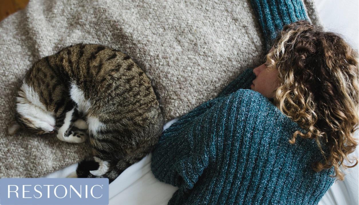 Woman sleeping next to her cat.