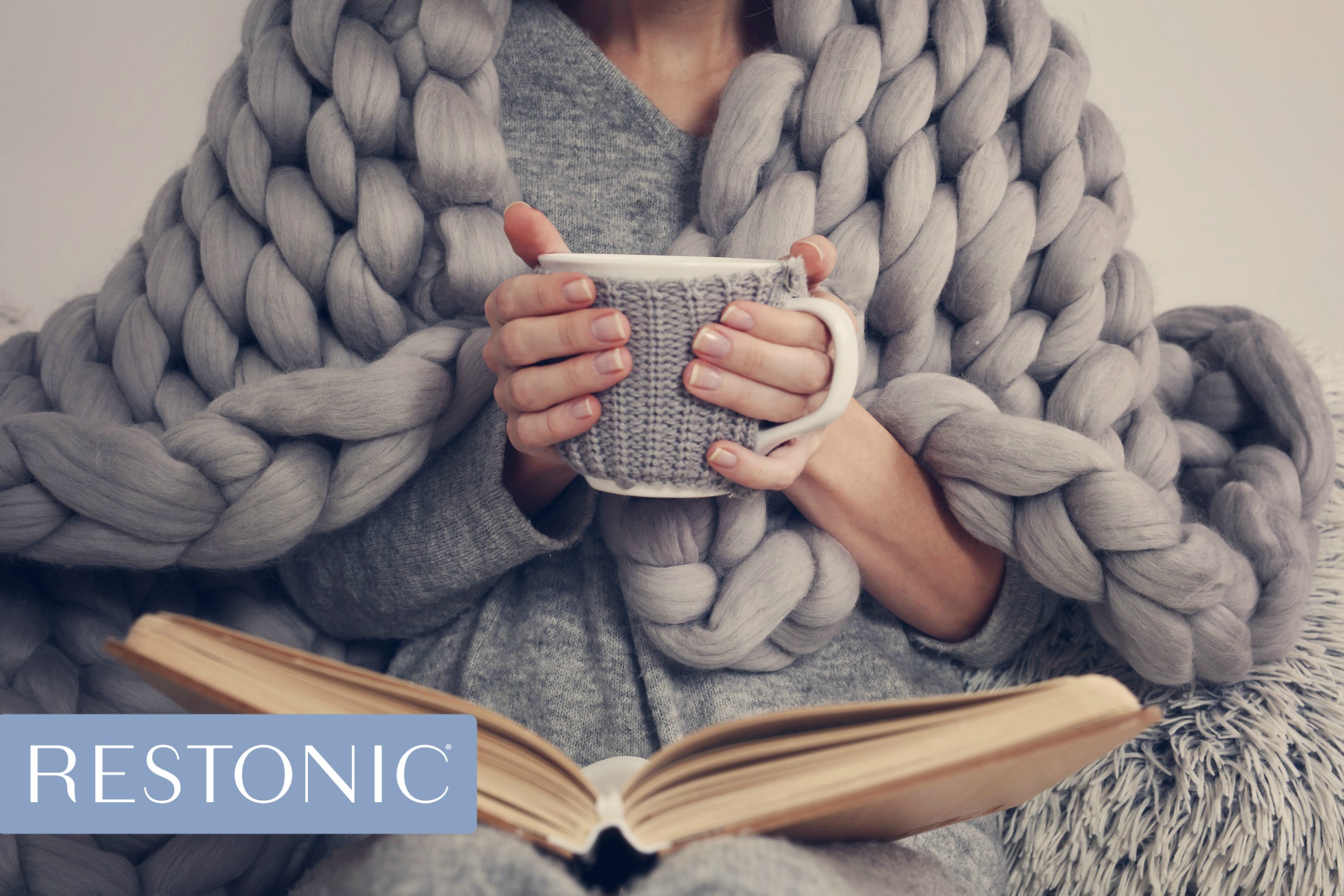 Woman wrapped in a cozy blanket, reading a book, and holding a cup as she readies herself for a great night of sleep.