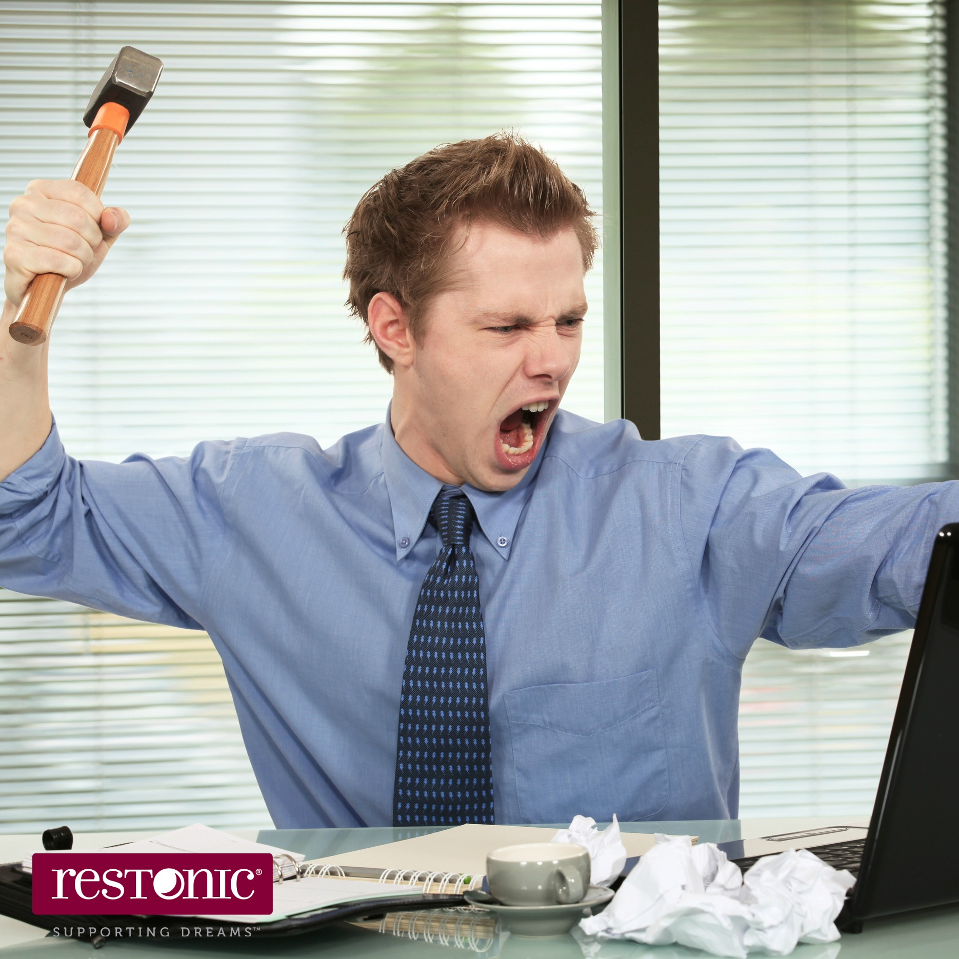 Anxious and sleep-deprived individual who is holding a hammer and screaming at his computer screen.