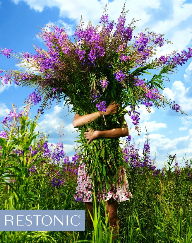Woman holding an armful of wildflowers and sniffing her way to a healthier lifestyle.