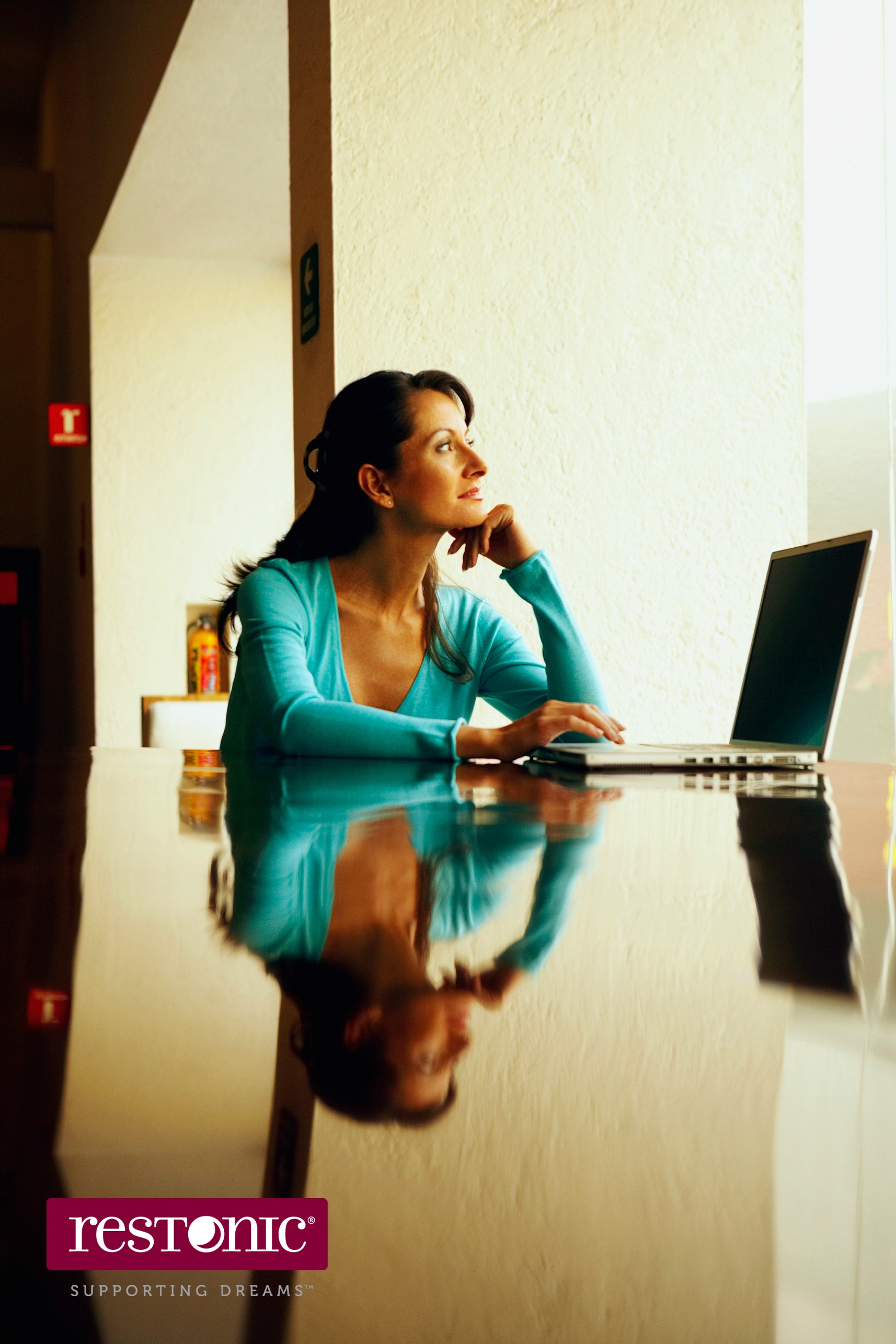 Woman sitting at a table using a laptop to read online mattress reviews prior to purchasing a new mattress.