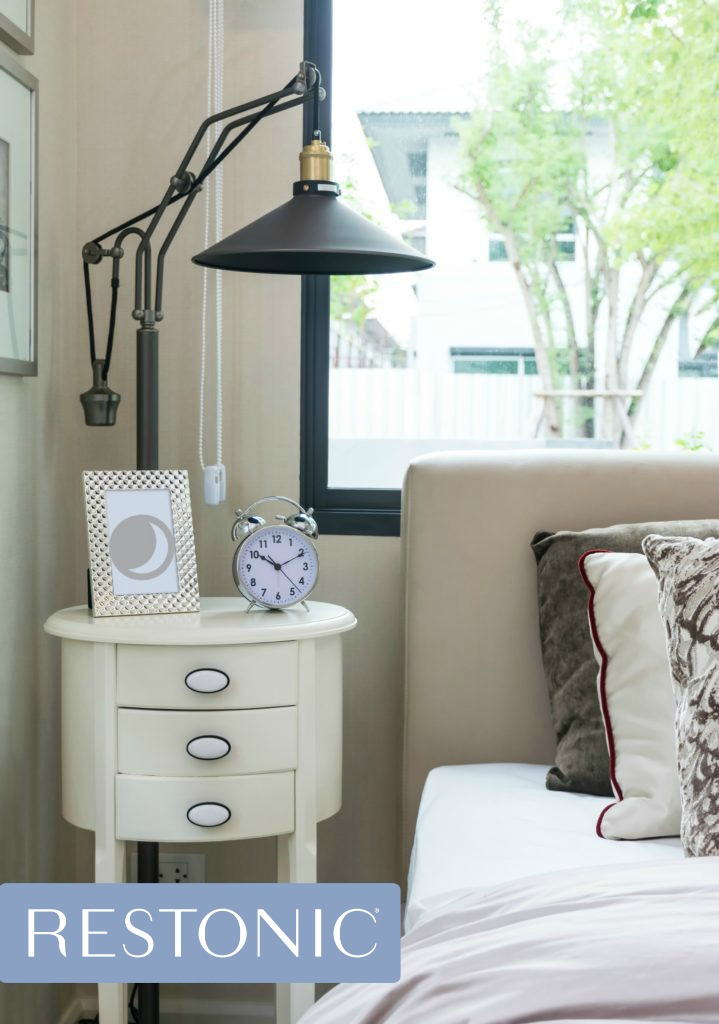 Nightstand with an alarm clock and photo frame on it.