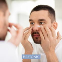 man using under-eye cream for skincare