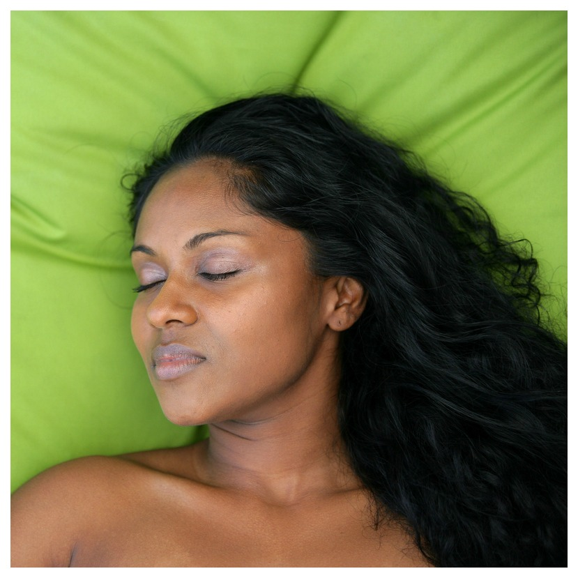 A woman with long black hair has made a health-boosting resolution as she gracefully rests on a green pillow.