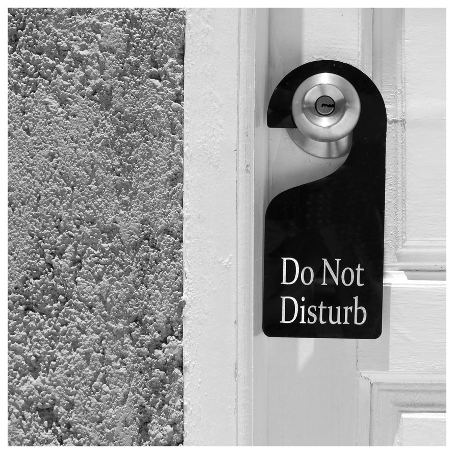 White door with a black Do Not Disturb helps establish a sleep ritual and the importance of a regular bedtime.