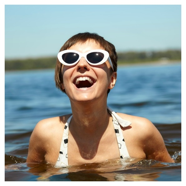 Woman wearing sunglasses and a bathing suit while she exercises to improve her quality and quantity of sleep.