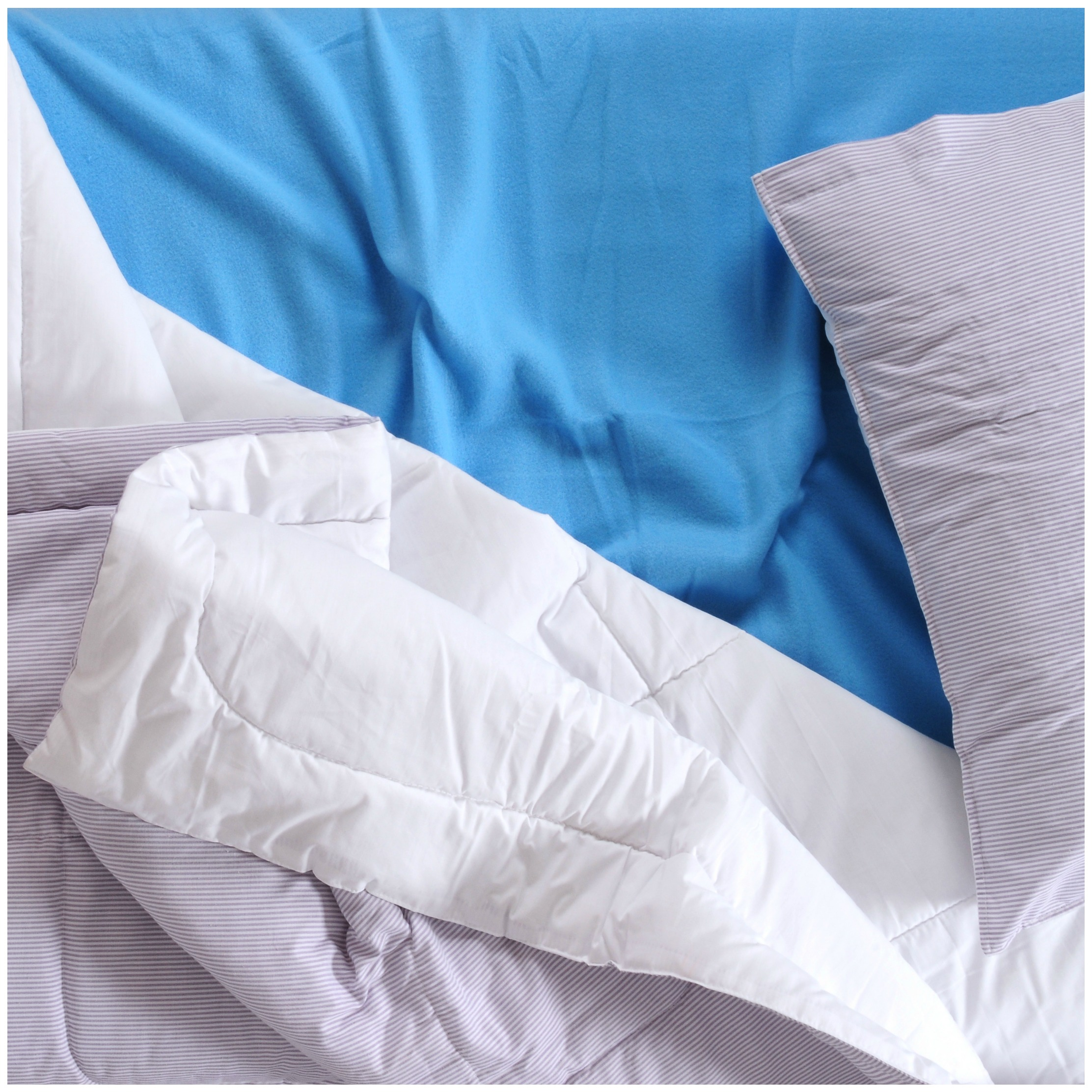 Blue bed sheet covered by a white comforter. Just one way to dial in comfort for healthy sleep as a New Year's resolution.