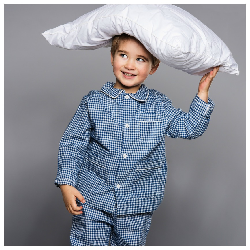 Boy dressed in pajamas and holding a pillow on top of his head. He knows that a supportive pillow will lead to better sleep.