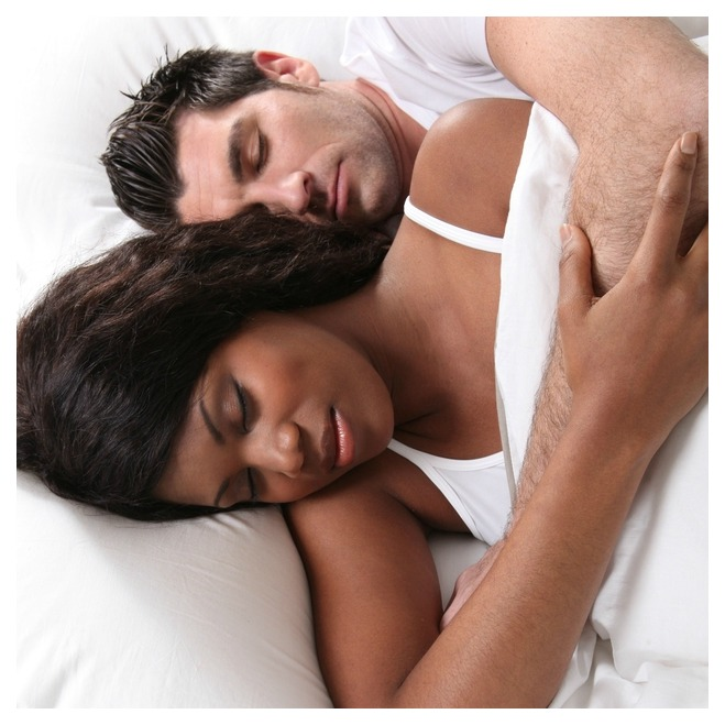 Man and woman sleeping in bed finding the best sleep position for their health.