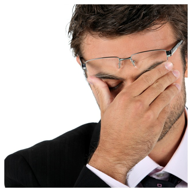 A stressed man wearing a suit and rubbing his eyes with his right hand.