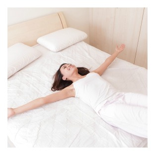 Woman comfortably maintaining her body temperature while laying down on a white bed with outstretched arms.