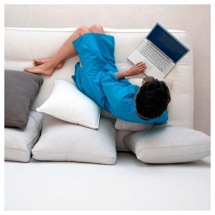 Woman wearing a turquoise dress and using a laptop while comfortably sitting on a white couch.