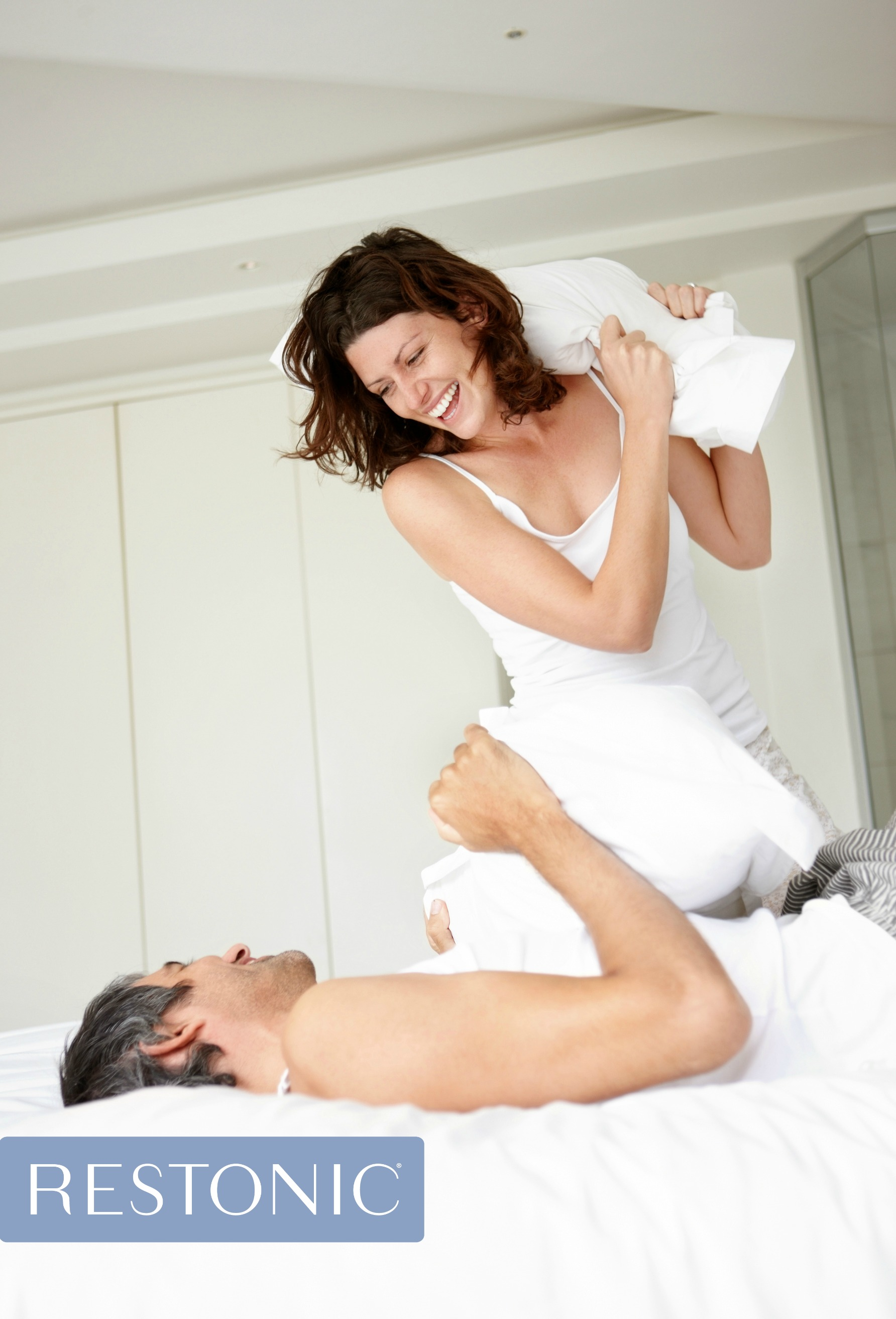 Man and woman in a jovial pillow fight while discussing what mattress is best for their body types.