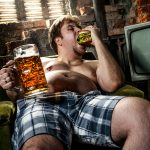 Man eating a burger and drinking a beer.