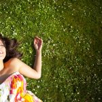 Woman wearing a flowery dress while laying on the grass.