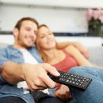 A husband and wife sitting on a couch watching television about how exercise will help them sleep better.