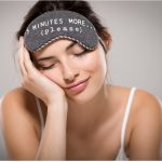 Woman closing her eyes with a sleep mask on her head.