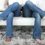 Two individuals sitting on a couch wearing blue jeans with their legs crossed.