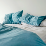 Unmade bed with blue pillows, white sheets, and blue comforter.