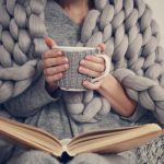 Woman wrapped in a cozy blanket, reading a book, with both hands holding a cup of coffee as she readies herself for a great night of sleep.