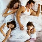A family of four sleeping in a bed together.