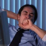 Man yawning while sitting at a computer. Is driving drowsy as dangerous as driving drunk?
