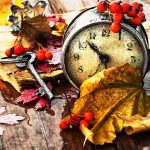 A clock in a pile of colorful fall leaves.