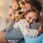 A young girl giving her father a hug with a Christmas tree in the background.