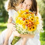 5 Steps for the Perfect Mother's Day | Young girl kissing her mother while holding a bouquet of flowers.