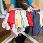 Woman sleeping on a pile of laundry after not getting enough sleep overnight.