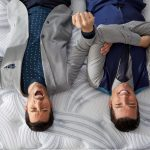 Jonathan and Drew Scott, the Property Brothers, laying upside down on a Restonic mattress.