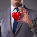 Man wearing a suit and holding a red heart between his fingers.