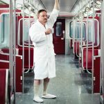 Man standing on a metro train in a white bathrobe.