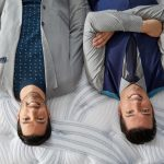 Jonathan and Drew Scott, the Property Brothers, lying on a mattress upside-down.