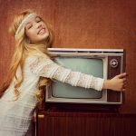 Young blonde girl hugging an old television set.