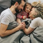 Man and woman lying underneath a weighted blanket which leads to better sleep.