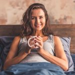 Beautiful young woman is holding a cup, looking at camera and smiling while lying in bed in the morning