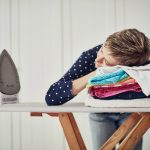 Woman resting her head on a pile of clothes that are stacked on an ironing board.