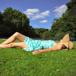 Woman wearing a sun hat and a flowered dress and laying on a grassy lawn.