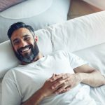 Bearded man smiling while laying on a bed.