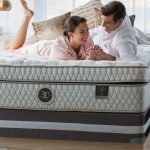 Man and woman talking on a bed about how their Restonic Mattress supports their dreams.