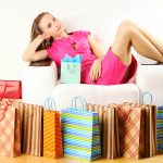 Girl sitting on a chair surrounded by Black Friday shopping bags.