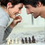 Couple playing chess together.